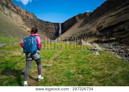poster of Woman traveler trekking in Icelandic summer landscape at the Hengifoss waterfall in Iceland. The waterfall is situated in the eastern part of Iceland.