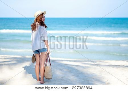 A woman holding bag and shoes while strolling on the beach with the sea and blue sky background poster