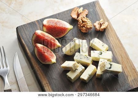 On A Wooden Board, Cheese With Blue Mold Dorblu, A Few Figs And Walnuts. There Are Cutlery Nearby. L