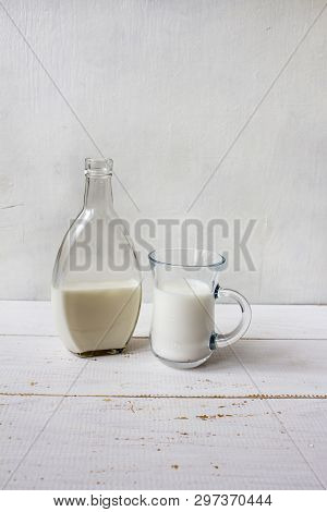 Delicious Fresh Milk On A White Wooden Background. A Bottle Of Milk And A Glass Of Milk. Copy Space
