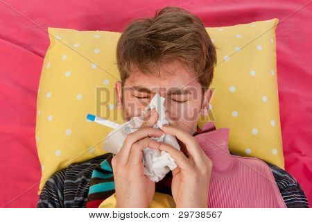 Very ill man is laying in his bed with warm water bottle and thermometer while blowing his nose