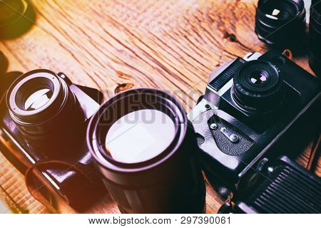 Old retro camera on vintage wooden boards abstract background with lens, close-up photo of old camera lens over wooden table, image is retro filtered, selective focus