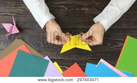 Man Made Origami Butterfly, Top View. Origami Figures, Colorful Paper And Male Hands. How To Make An