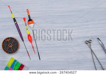 On A Gray, Wooden Table Set Of Items For Fishing, Sinkers, Floats, Fishing Line, In The Center There