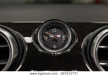 The Watch On The Dashboard Of An Expensive Car Is Close-up, Covered With Natural Black Leather And B