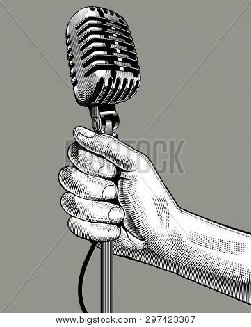 Hand with a retro microphone. Vintage engraving stylized drawing