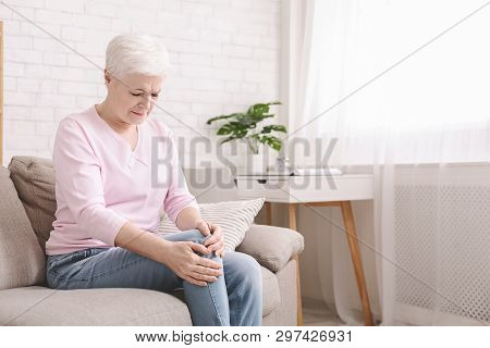 Health Problems Of Old Age. Senior Woman Suffering From Pain In Leg, Massaging Her Knee At Home, Emp