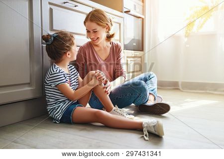 Family Mother And Child Daughter Hugging In Kitchen On Floor