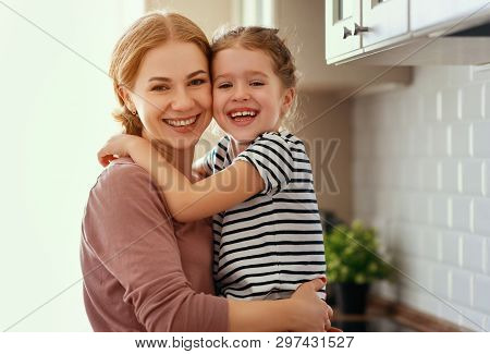 Family Mother And Child Daughter Hugging In Kitchen  .