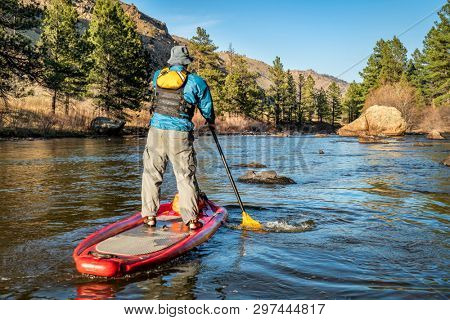 senior male paddling inflatable stand up paddleboard on a mountain river - Poudre RIver in Colorado in spring scenery with low water flow