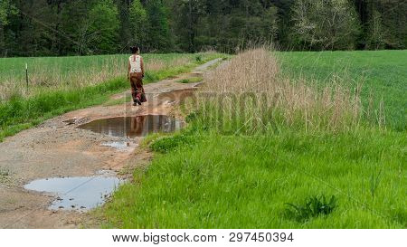 Back of woman in sarong walking away  on dirt road with puddles in field poster