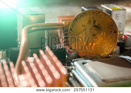 Golden physycal bitcoin near the computer components. Business concept of digital bitcoin cryptocurrency. Blockchain technology and bitcoin mining business concept