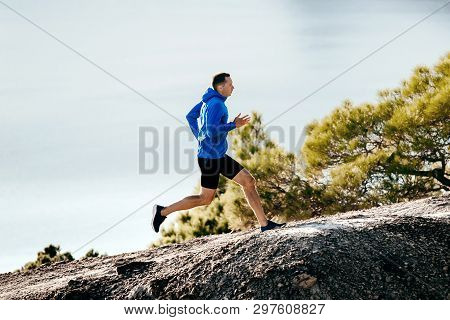 Man Runner In Blue Jacket Running Uphill Background In Sky