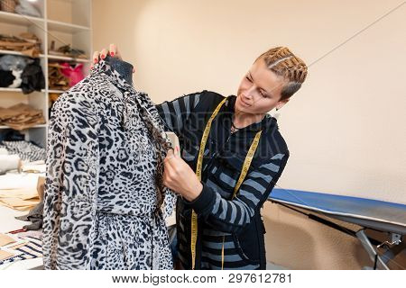 Dressmaker with mannequin as professional fashion designer. female dressmaker adjusting clothes on tailoring mannequin and smiling. poster