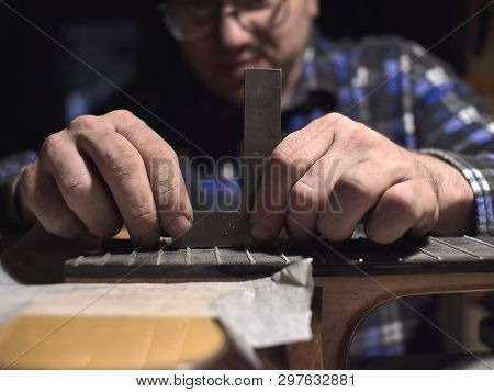 Installation Frets On The Neck Of The Guitar. Specialist Checks The Level Of Frets.