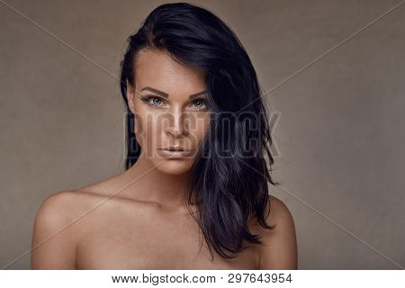 Beautiful Middle-aged Woman With Bare Shoulders And Her Long Dark Hair Swept Over One Shoulder Looki