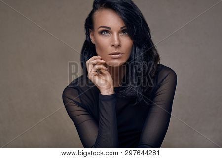 Beauty Portrait Of An Attractive Middle-aged Woman In Black Top With Long Dark Hair Looking Thoughtf