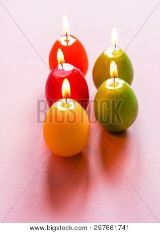Traditional Easter decor. Group of bright burning paraffin candles in the shape of colorful eggs on soft pink background. poster