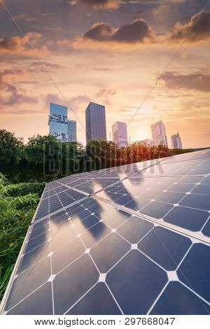 Ecological energy renewable solar panel plant with urban landscape landmarks in sunset