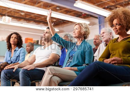 Woman Asking Question At Neighborhood Meeting In Community Center