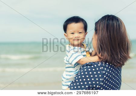 Portrait Of Asian Happy Family Loving Mother And Her Baby Outdoors Near Sea. Summer, Vacation, Trave