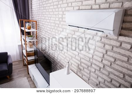 White Air Conditioner Blowing Cold Air On Brick Wall In Living Room