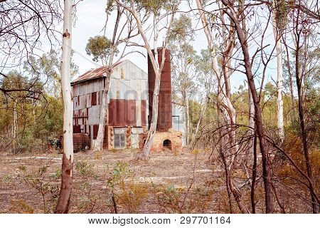 An Old Disused Shed With Kiln And Chimney Stack Standing Alone In The Dry Australian Bush