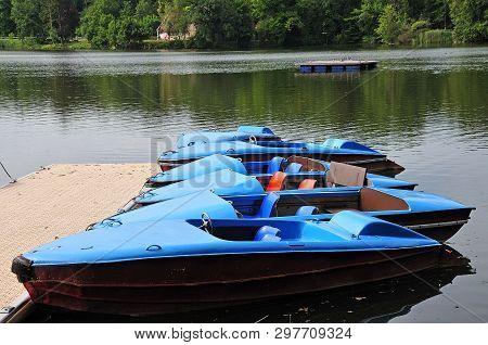 Row Of Blue Paddleboats Lying At Jetty At A Lake In Summer