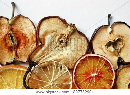 Dried Slices Of Apples, Pears And Various Citrus Fruits Closeup Against A White Background With Spac