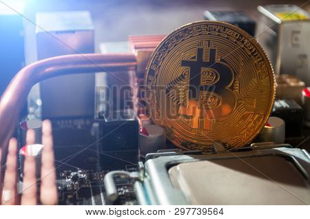 Golden bitcoin on the motherboard, closeup. Business concept of digital bitcoin cryptocurrency. Blockchain technology, bitcoin mining concept