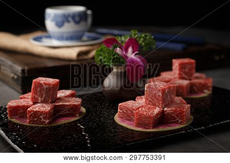Kobe Beef Cubes In A Black Ceramic Dish