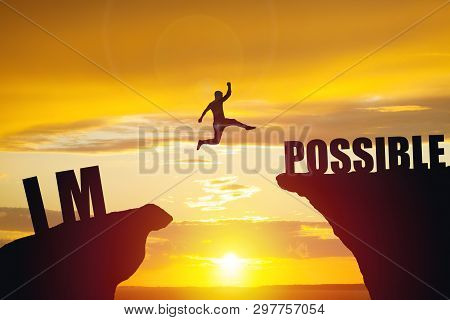 Man Jumping Over Impossible Or Possible Over Cliff On Sunset Background