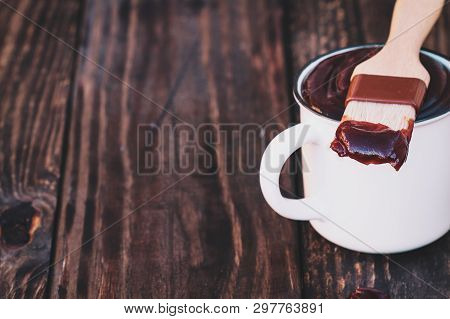 Bbq Brush With Barbecue Sauce On The Tip Resting On A White Cup Over A Rustic Wood Background With D