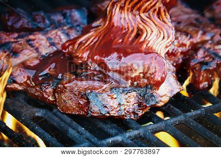 Boneless Beef Ribs Grilling Over Flames With Barbecue Sauce Added With Bbq Mop. Extreme Shallow Dept