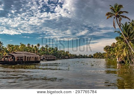 Backwater View In Day At Alleppey Kerala India With White Cloud, Blue Sky And Palm Tree.