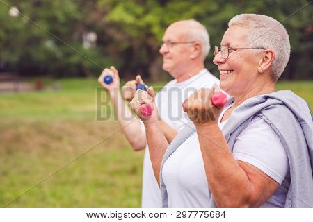 Together We Workout Better - Smiling Couple Practice With Dumbbells In A Park