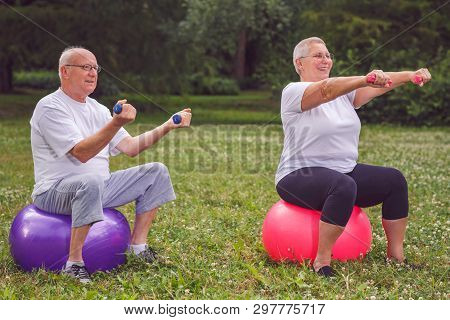 Smiling Senior Sports Couple Sitting On Fitness Ball With Dumbbells