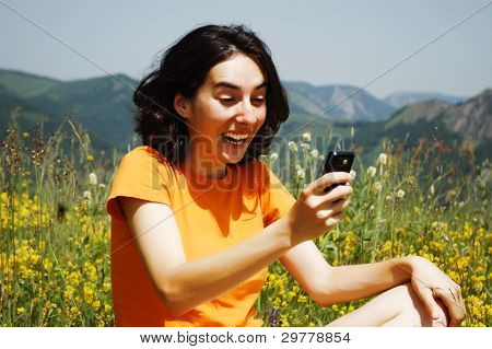 Young woman enjoying the outdoors using her cell phone
