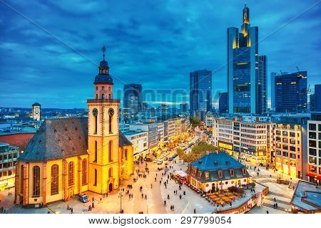 View To Skyline Of Illuminated Frankfurt Am Main During Twilight Sunset. St. Catherines Church And T