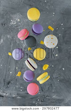 Falling Colorful Macarons Cakes With Raspberries And Blueberries On The Background Of Concrete Wall.