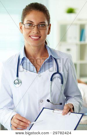 Retrato de seguro médico femenino con portapapeles mirando a cámara