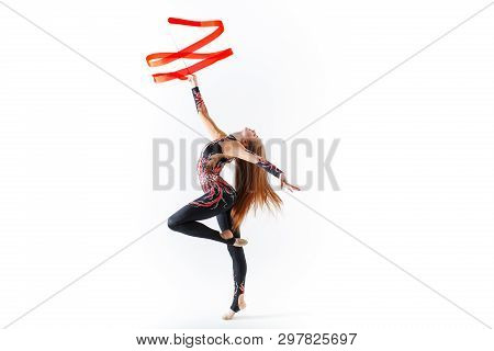 Rhythmic gymnastics. Young gymnast girl with red ribbon on white background poster