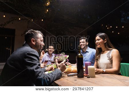 Mid Adult Man Holding Wineglass While Gossiping With Pals At Weekend Dinner Party