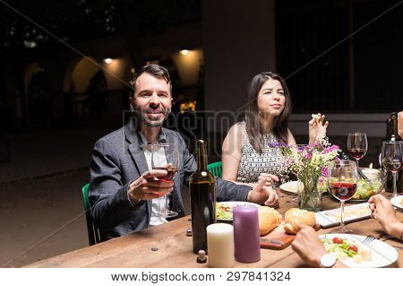 Portrait Of Smiling Man Having Wine While Enjoying Dinner Party With Pals In Backyard