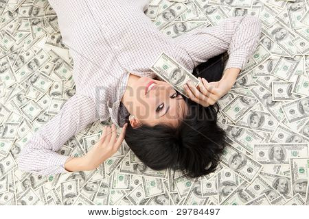 Young business woman resting upon money