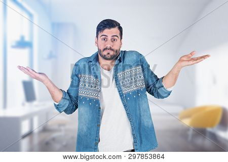 Shrugging Shoulders Caucasian Man In Casual Clothes Standing In Blurred Home Office. Concept Of Doub