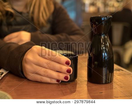 Woman with painted fingernails holding a sake glass next to black bottle in restaurant poster