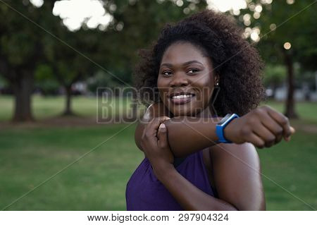 Portrait of happy curvy african woman stretching arms in park. Confident oversize young woman with curly hair smiling while exercising outdoor. Sporty african american girl training outdoors.