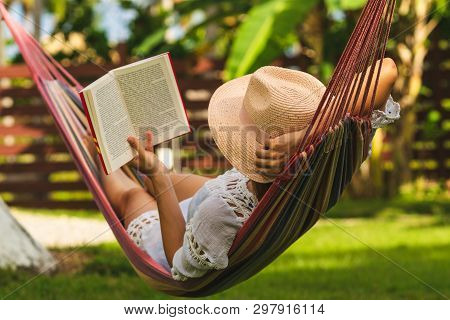Beautiful Woman Relaxing In Hammock. Beautiful Woman Reading Book In Hammock. Happy Beautiful Woman