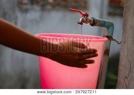 Young Hands Collecting Water With A Plastic Bucket From An Old Slow Flowing Water Tap With Great Pat